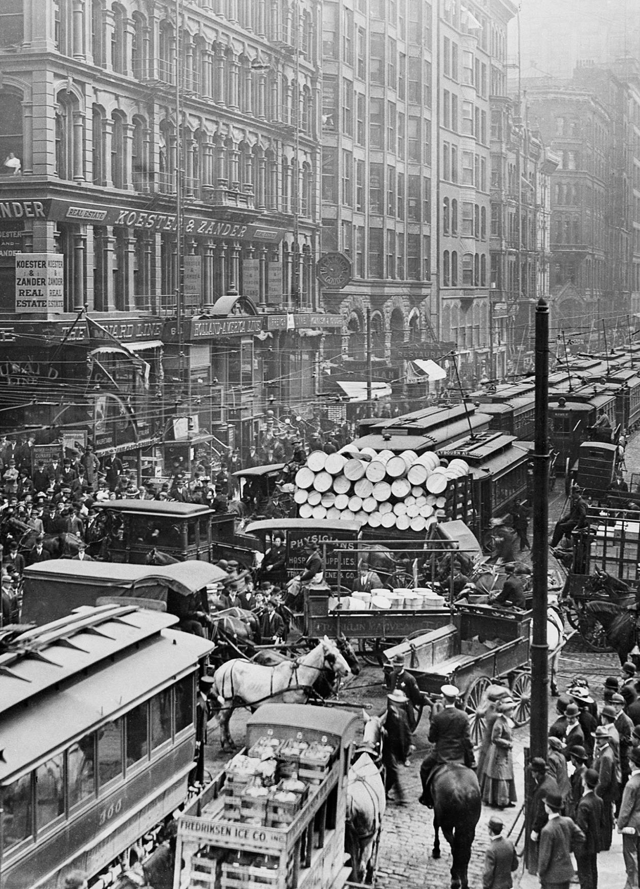 Streetcars, trucks and cars fight to cross an intersection, while crowds of pedestrians move around the gridlock