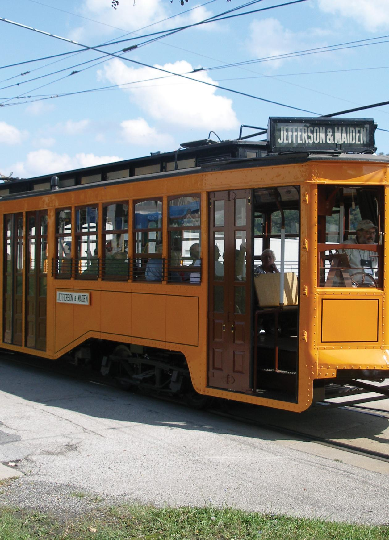 Color photo of a yellow trolley making its way.