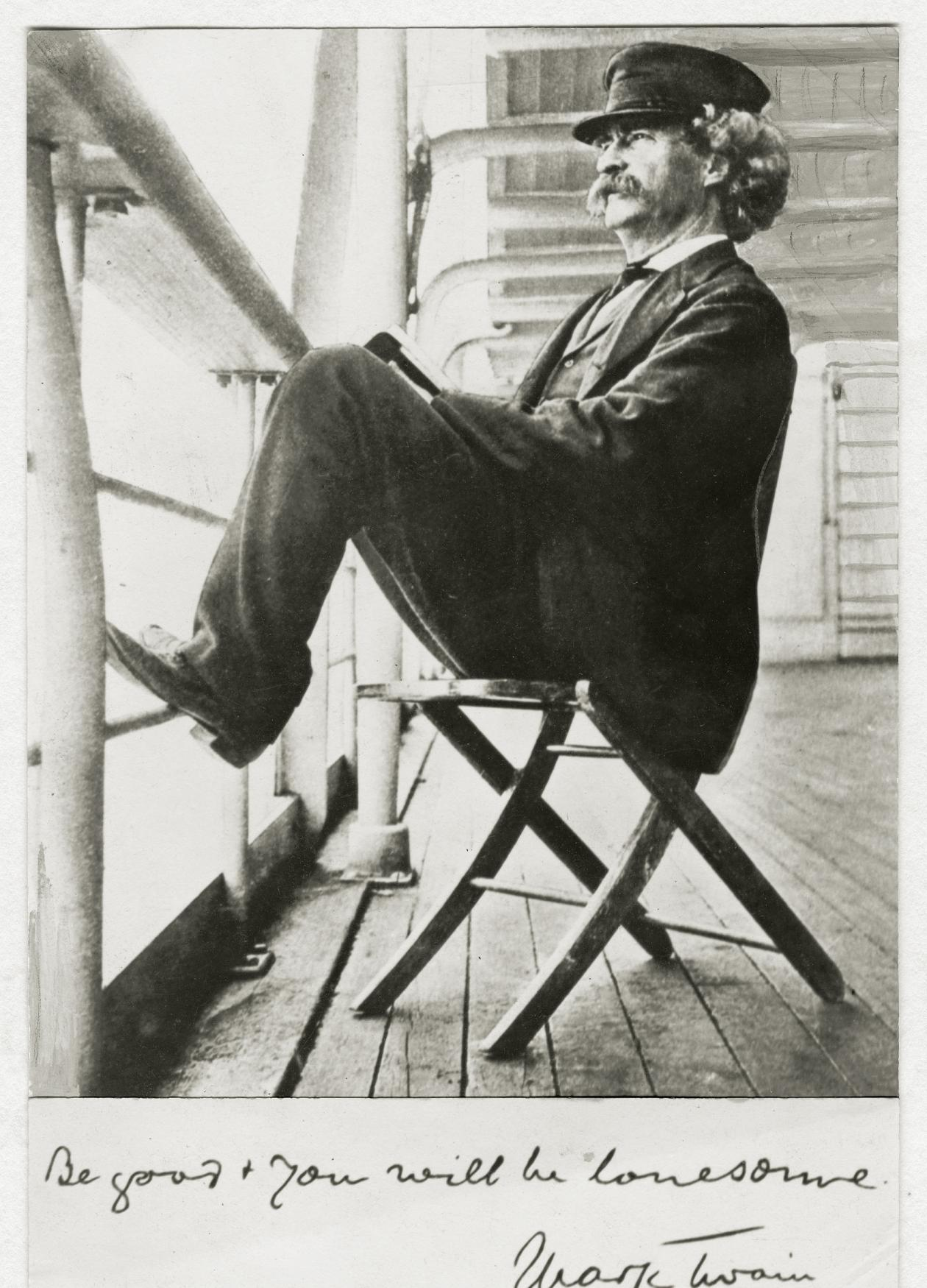 Black and white photo of Mark Twain sitting on a chair on the deck of a cruise ship.