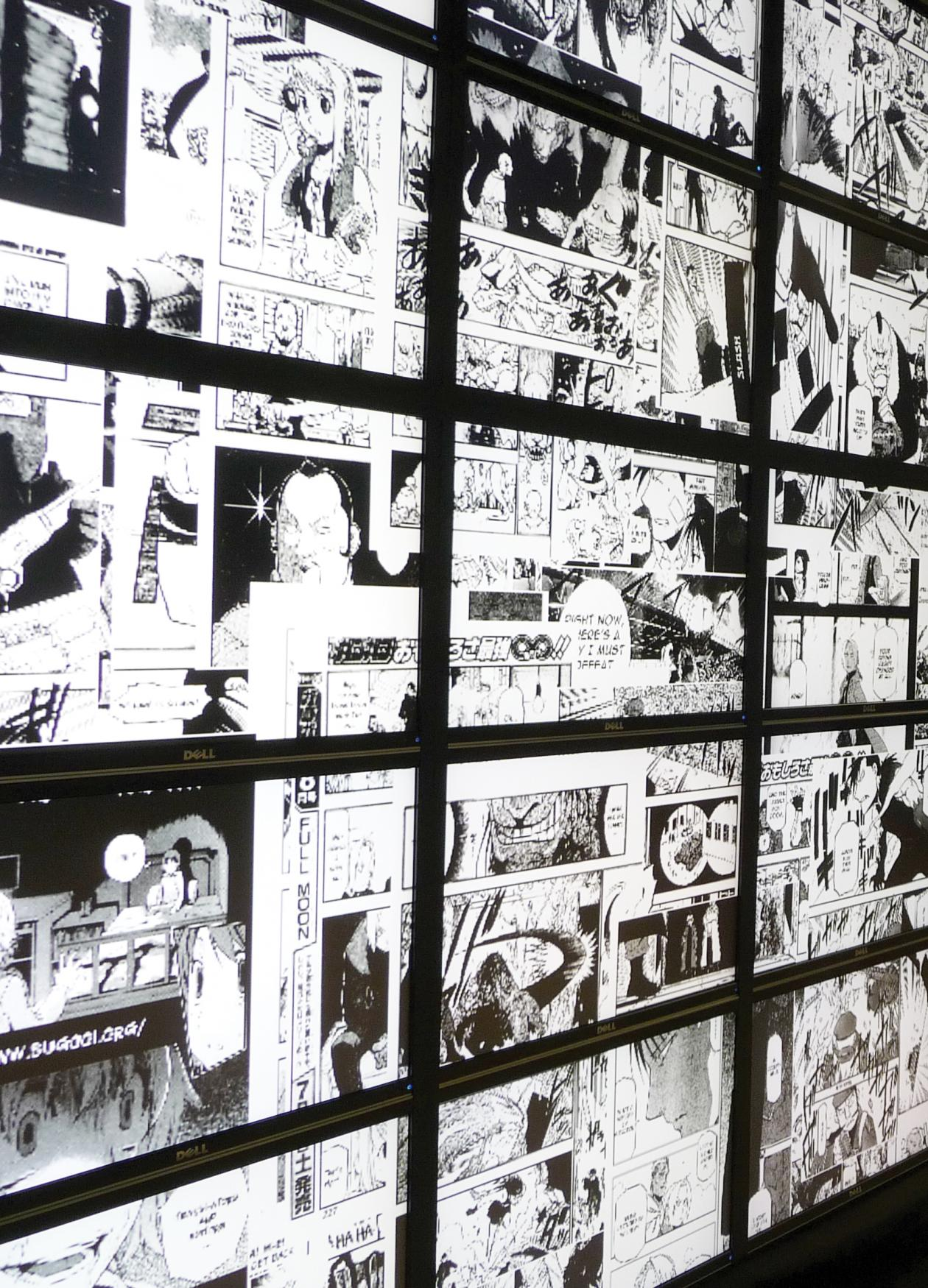 Two men stand in front of numerous small screens lit up with black and white manga illustrations