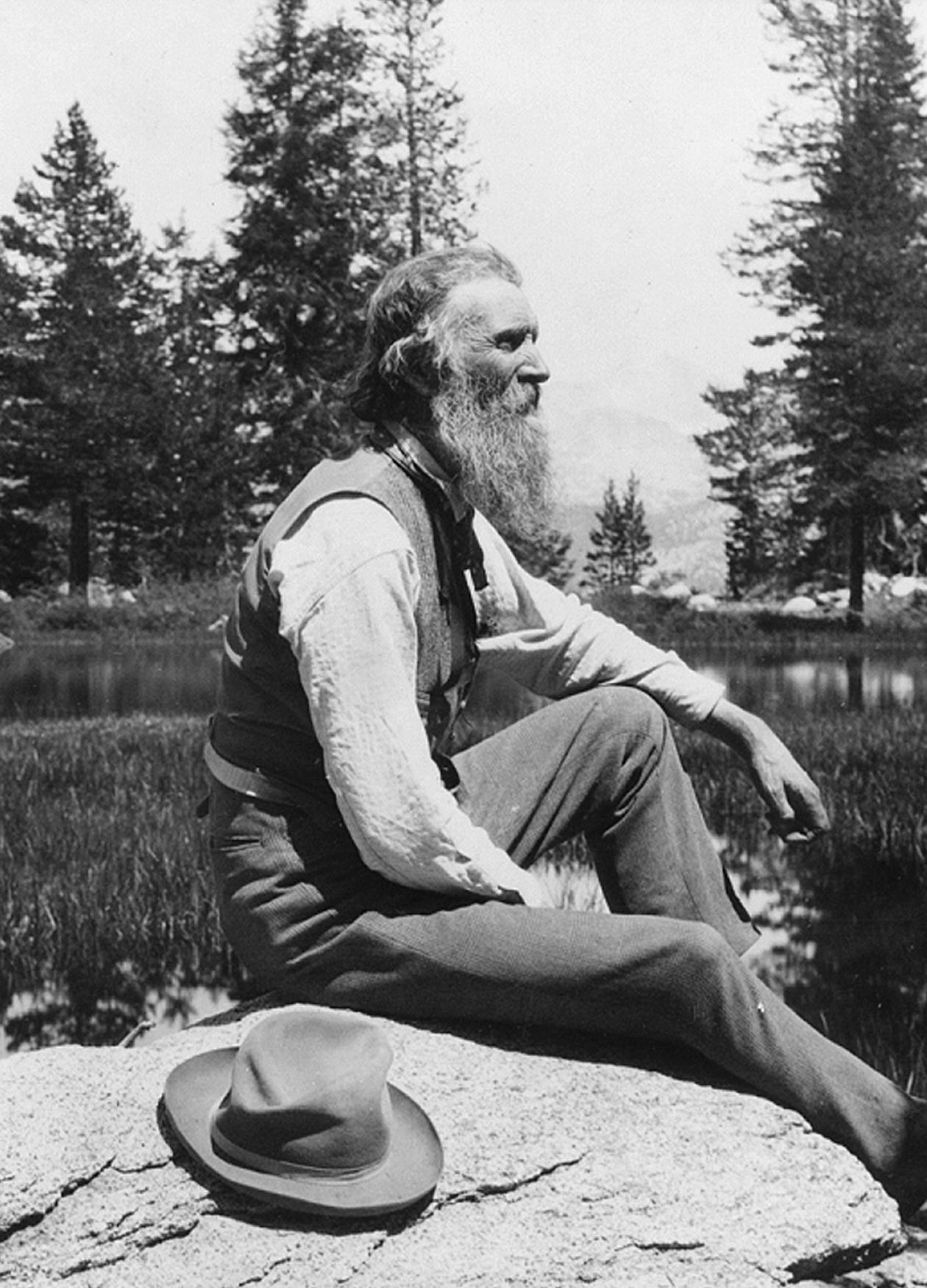 Muir sitting on a rock next to a lake, with a long gray beard, hat resting next to him