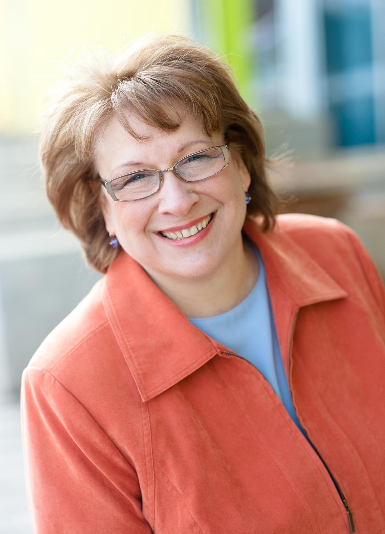 Color photo portrait of Maggie Coval in a long-sleeved orange blazer.