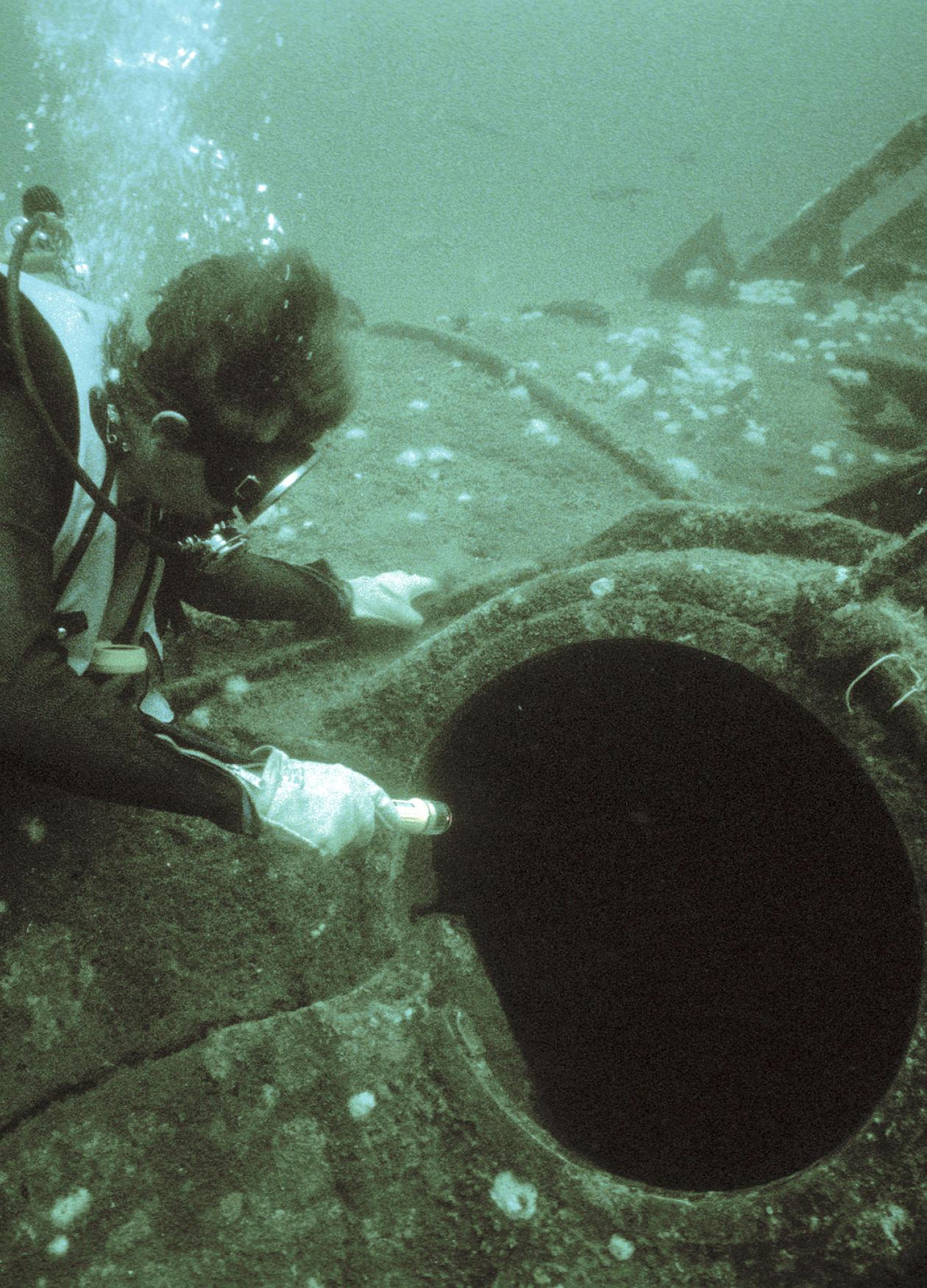 Photo of a scuba diver pointing at the torpedo loading hatch of a sunken submarine.