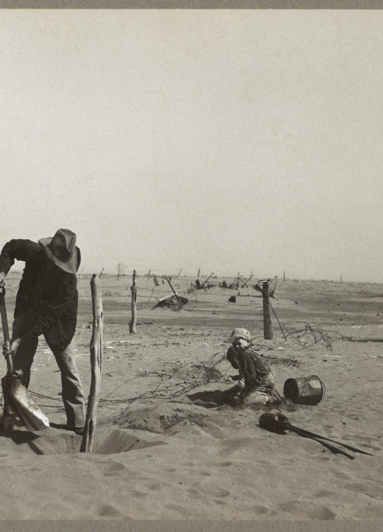 Black and white photo of a man shoveling sand in the foreground, with a child to his right, sitting on the plain, and a cow further in the distance.