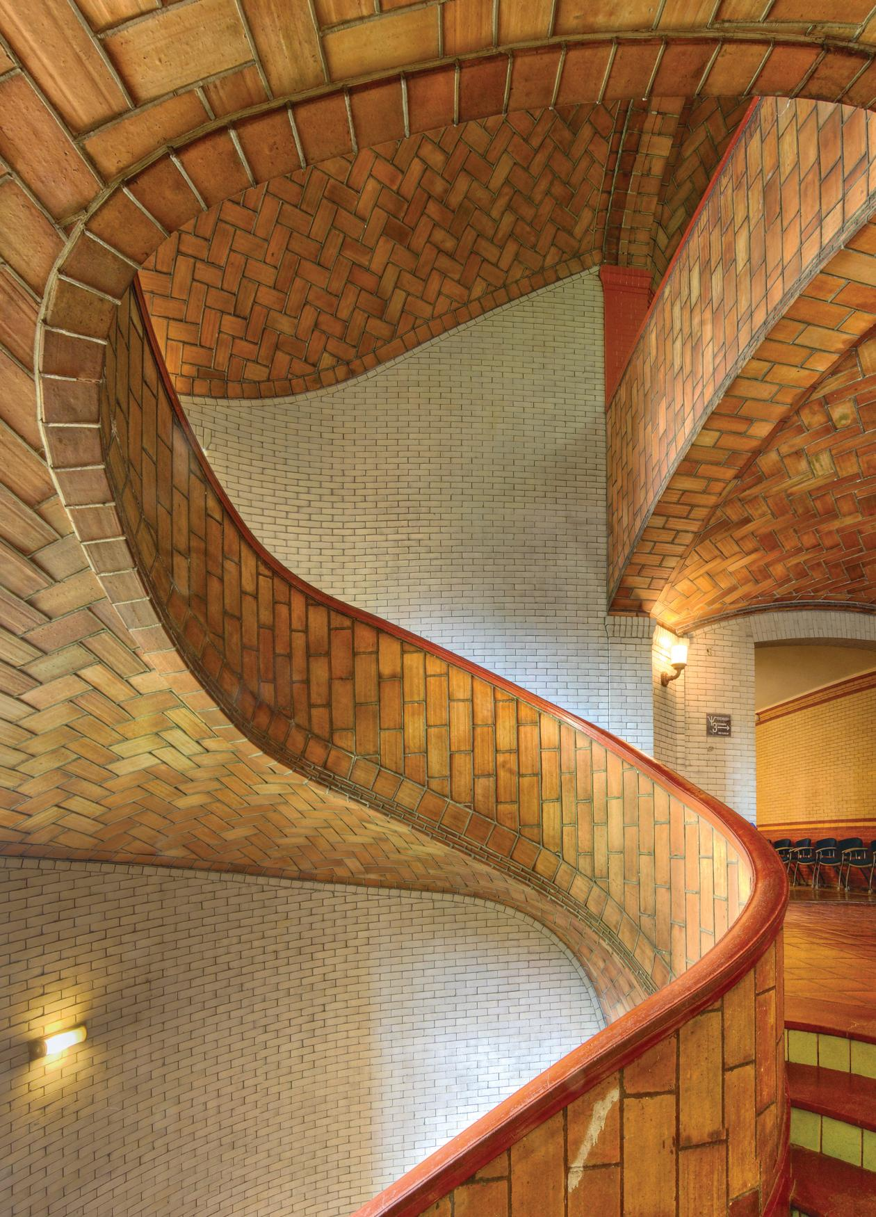 Photo of an ornate, red brick spiral staircase.