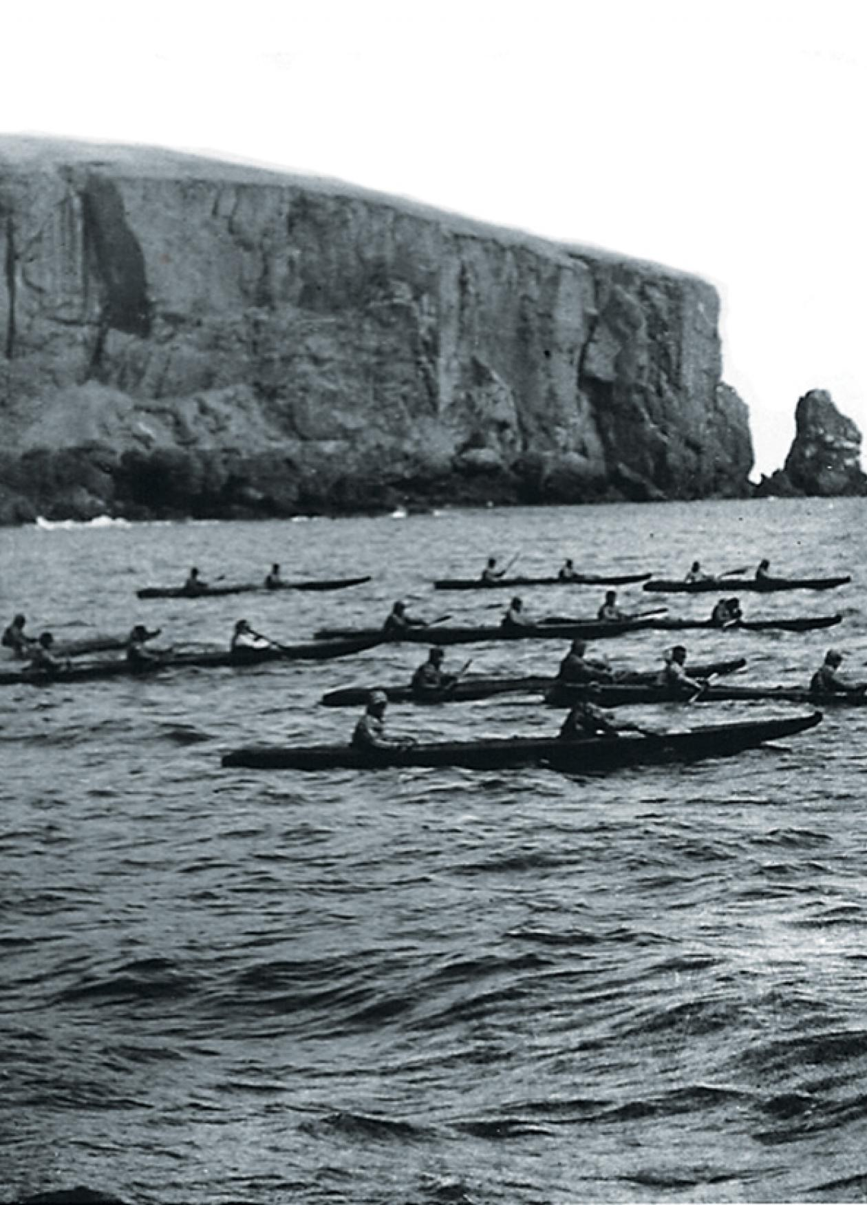 Several small boats with rowers, on the water, off the coast of an island with a large plateau