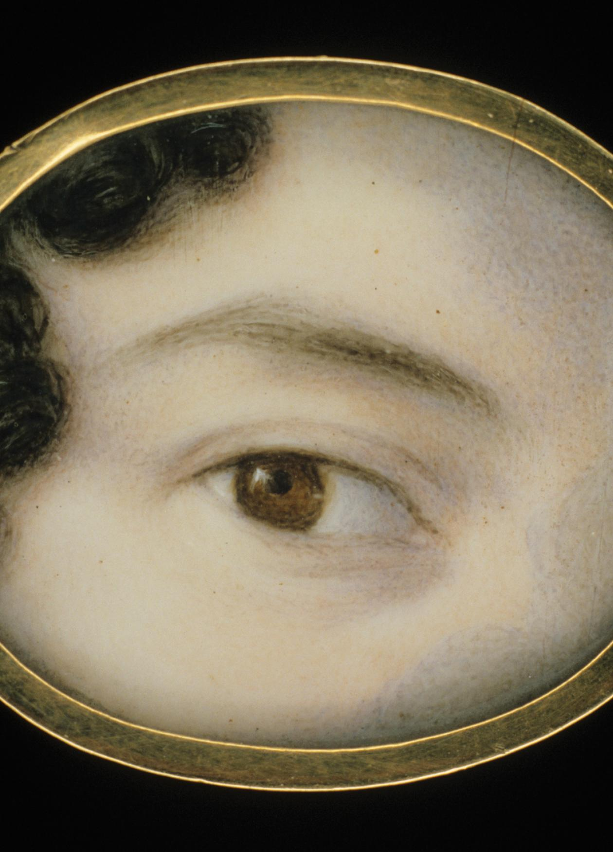 close up of a woman's brown eye, framed by a thin dark eyebrow and pale skin