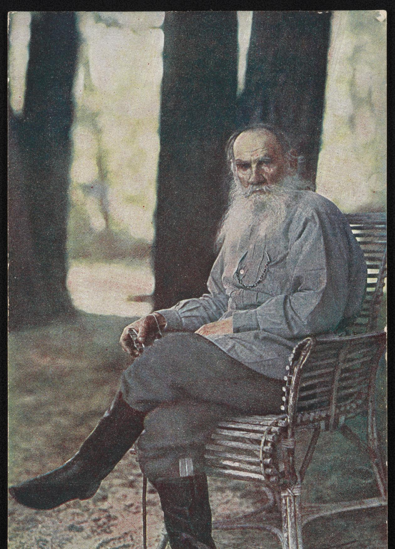 Tolstoy in a blue shirt and boots, long white beard, sitting under trees on a wood bench