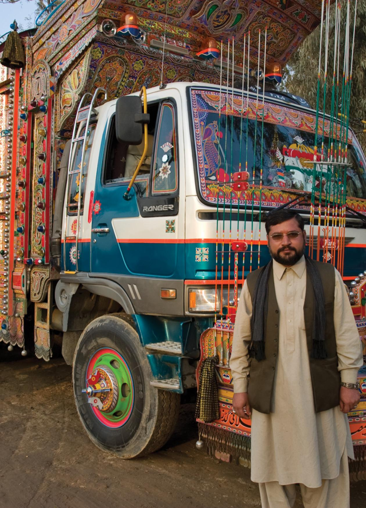 Pakistani man standing in front of a truck