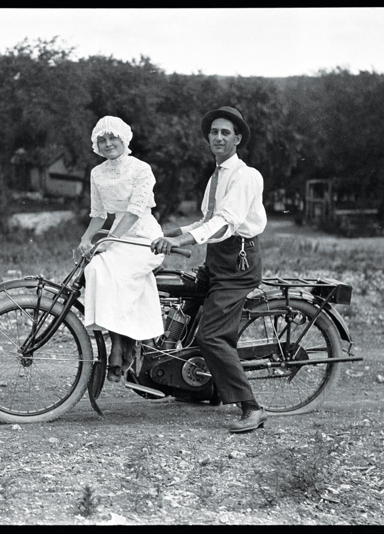 Kratzer, in a white shirt and black hat, sits on a motorcycle behind a woman in a white dress and cap, on a dirt road