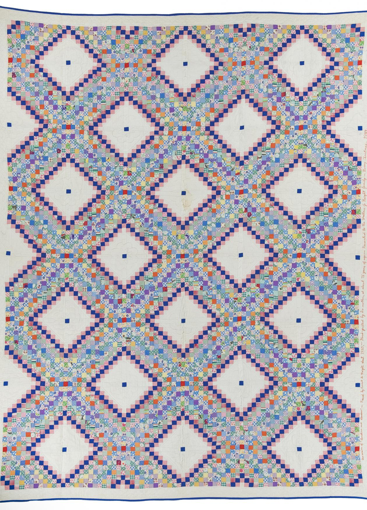 A multicolored quilt, edged in dark blue, with a pattern of white squares outlined with blue and pink dots