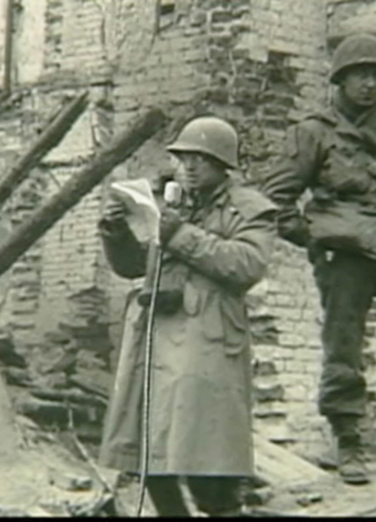 Three armed and uniformed soldiers watch Plambeck, also uniformed, speak into a microphone while reading off of a paper, in the ruins of a stone building