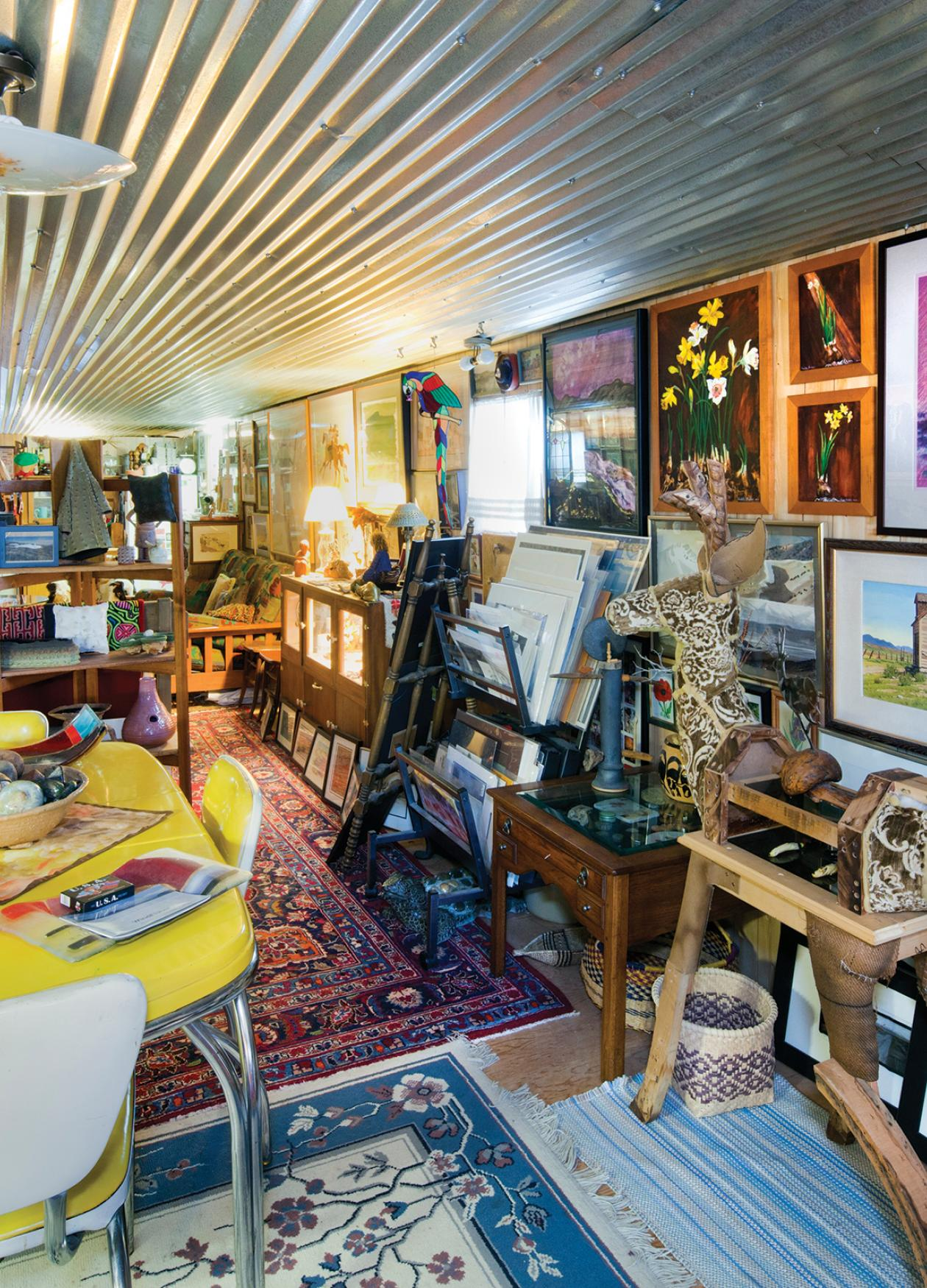 Color photo of an art gallery filled with paintings and artifacts of all types.