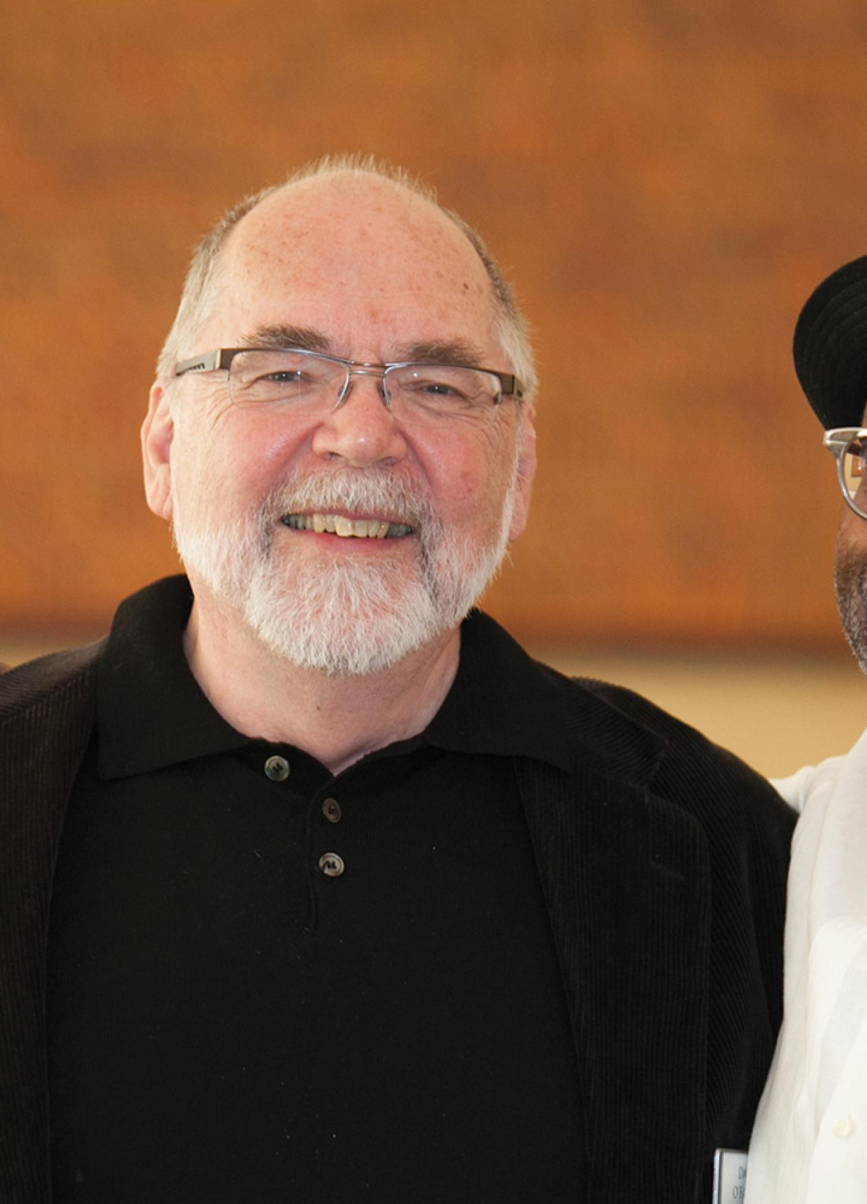 O'Fallon, black turtleneck and glasses, and Jones, wearing a black hat and glasses