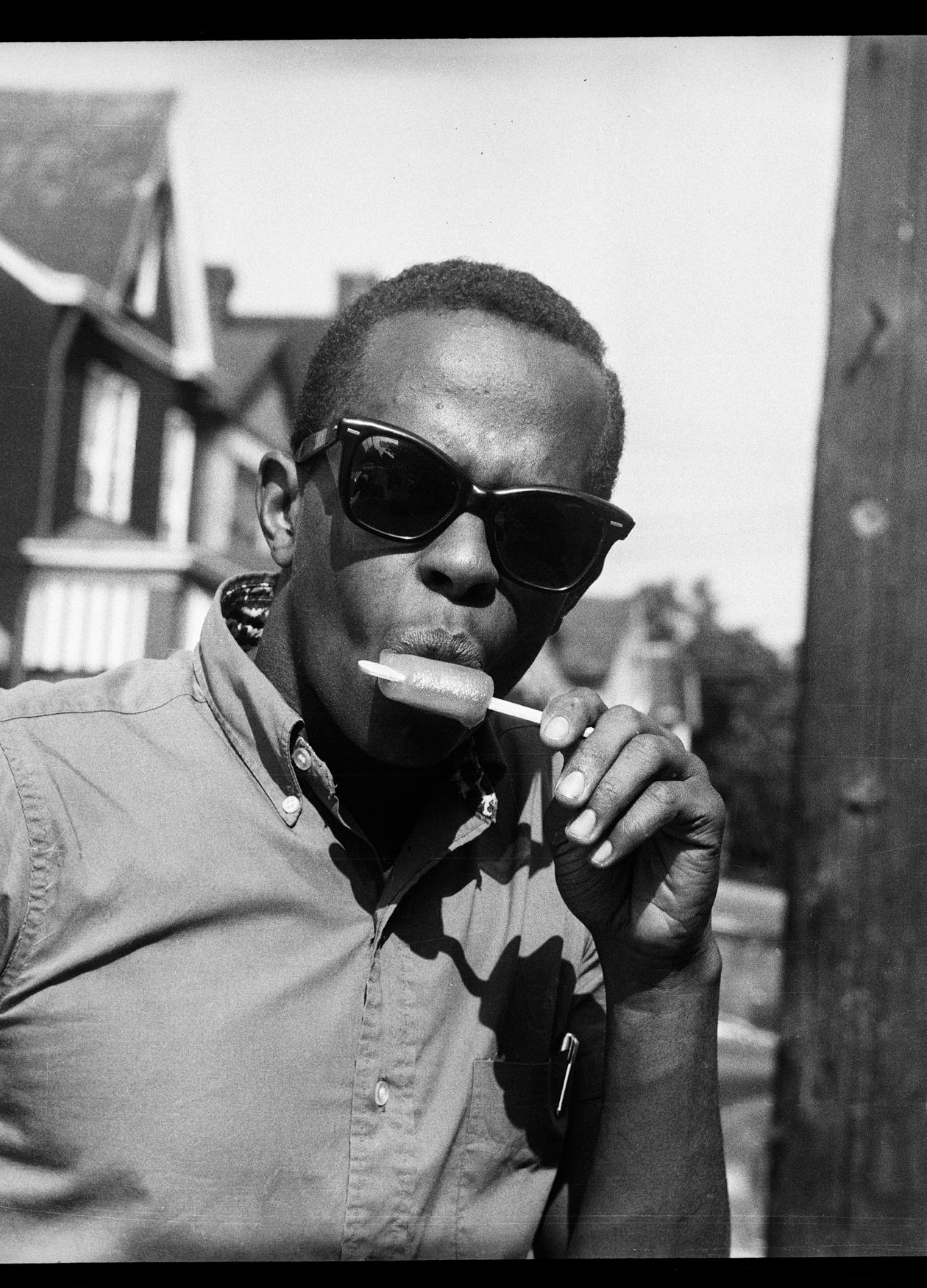 A young, African American man wearing sunglasses and eating a popsicle
