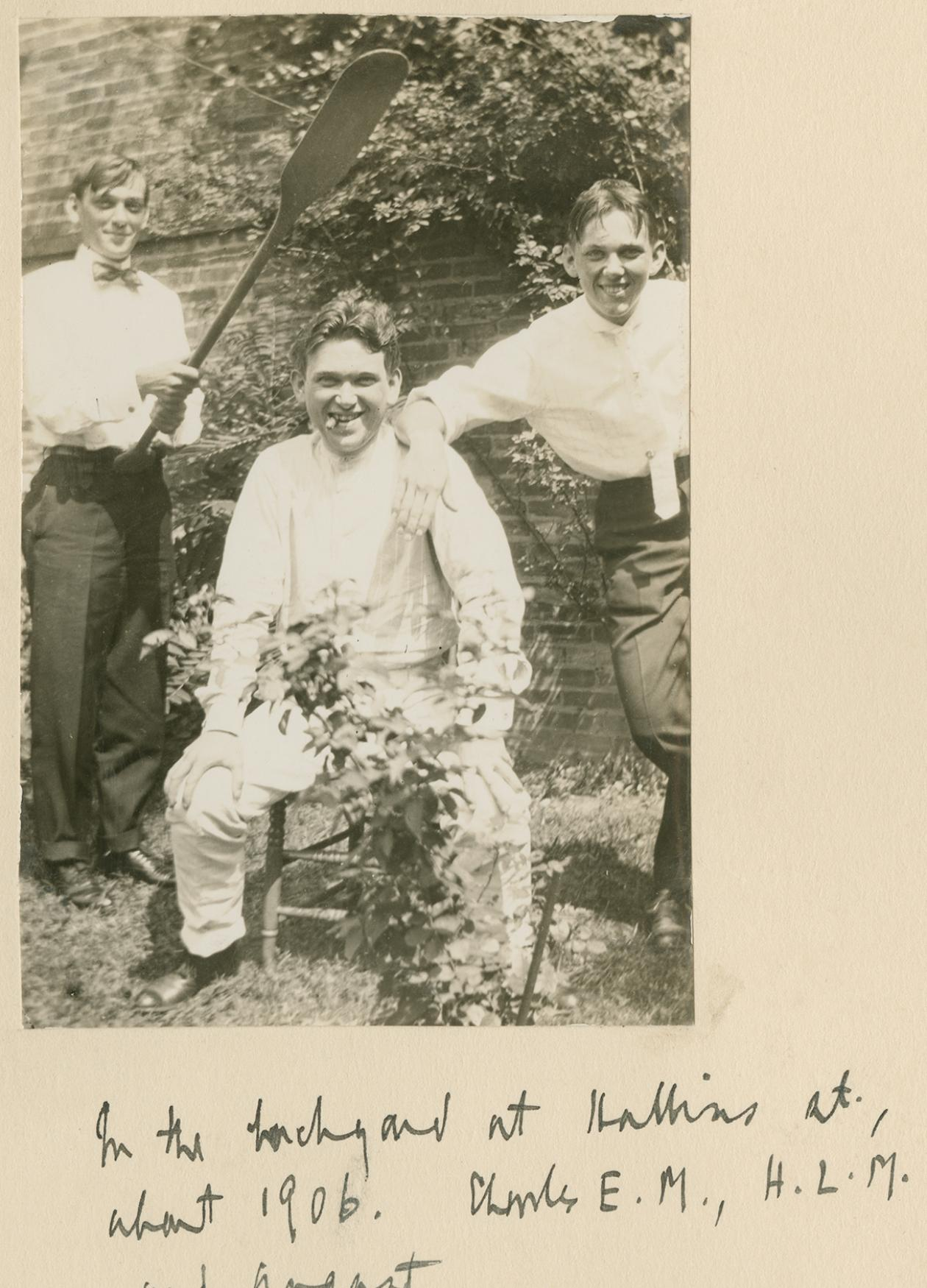 An old photograph of the Mencken brothers in their backyard. One of them is holding an oar over H.L. Mencken's head.