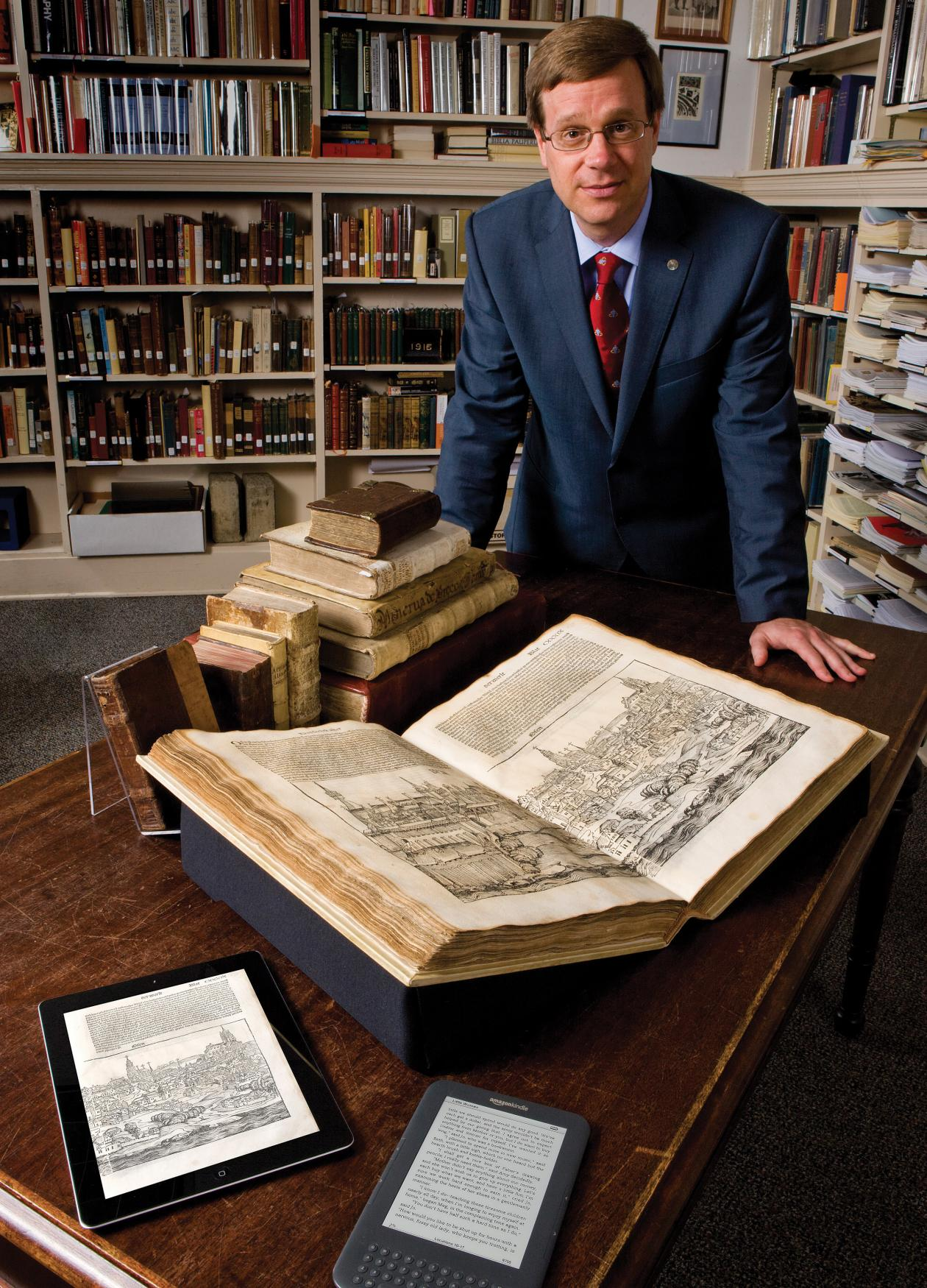 Photo of a man in a suit leaning over a rare book in a library, while looking at the camera.