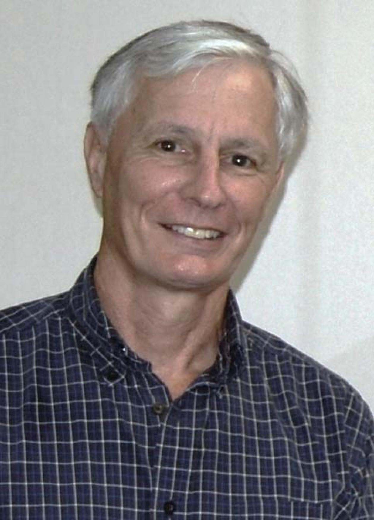 Russell, with white hair, wearing a black and white grid patterned shirt