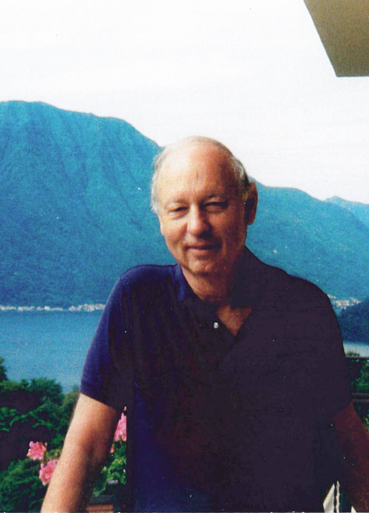 Color photo of Jules Witcover standing on the balcony of a house which overlooks a large bay and mountains in the background.