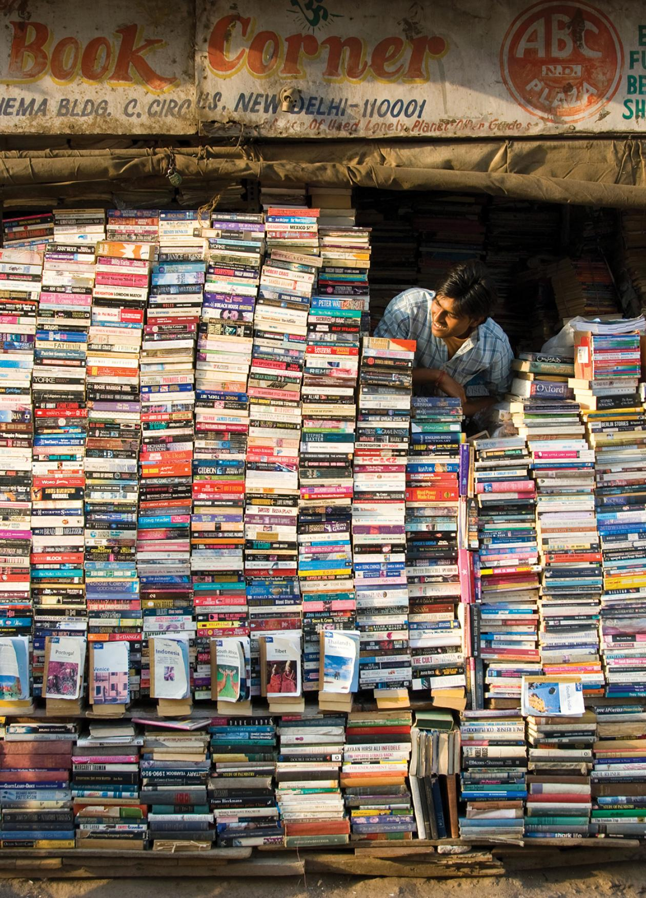 Color photo of a man in Delhi, India, peering out from behind a wall of books which comprises his storefront.