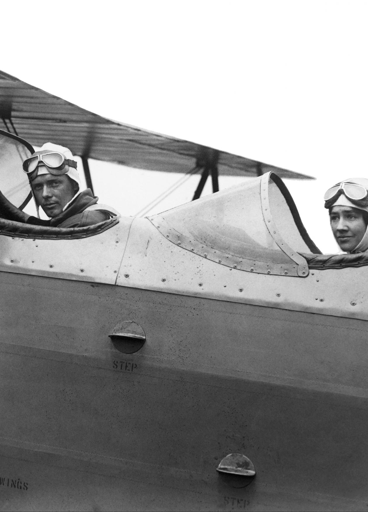 Black and white photo of the Lindbergh brothers in an airplane with an open cockpit.