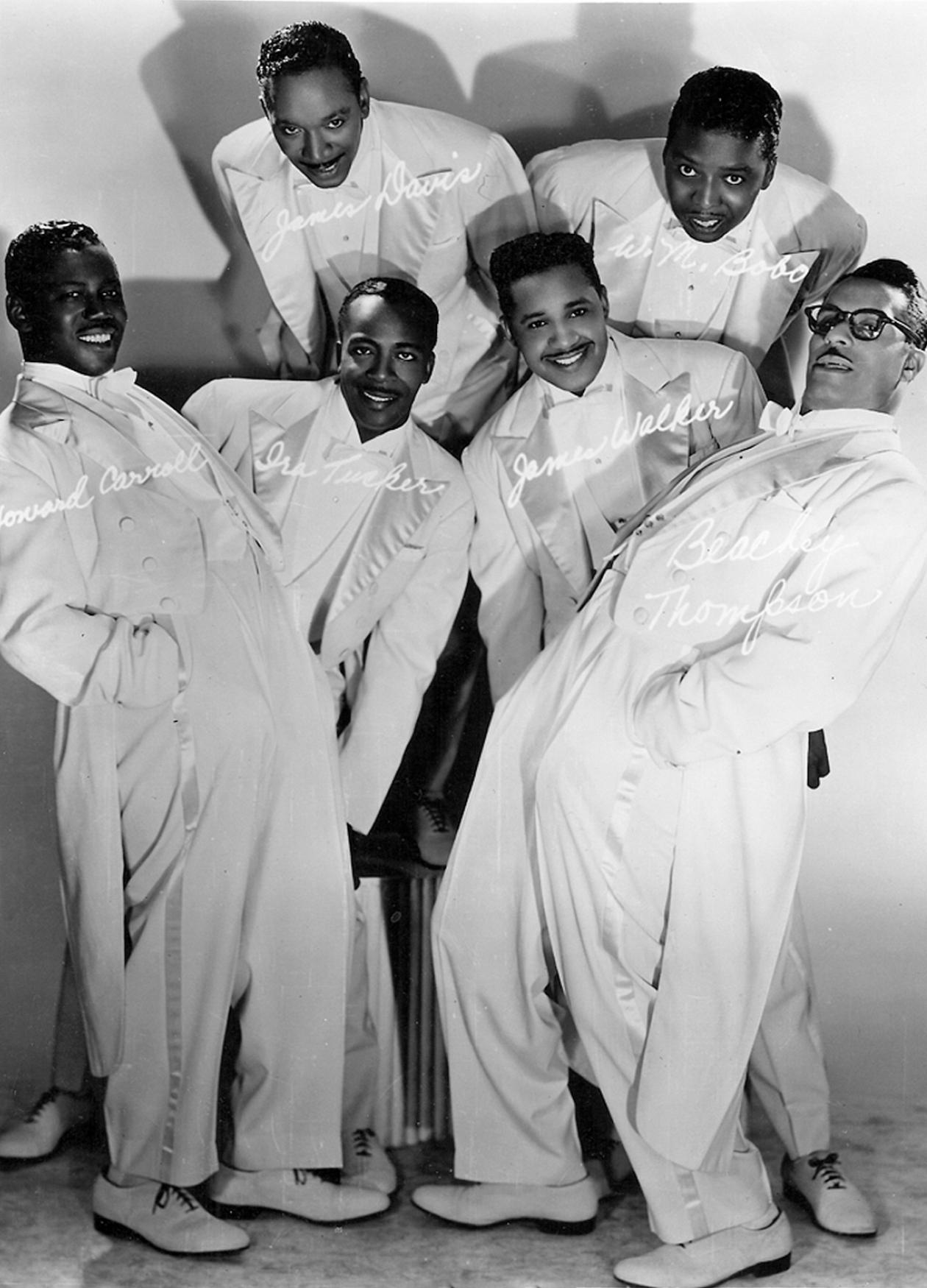 Black and white photo of a musical group wearing white tuxedos and posing for a photograph at irregular angles.
