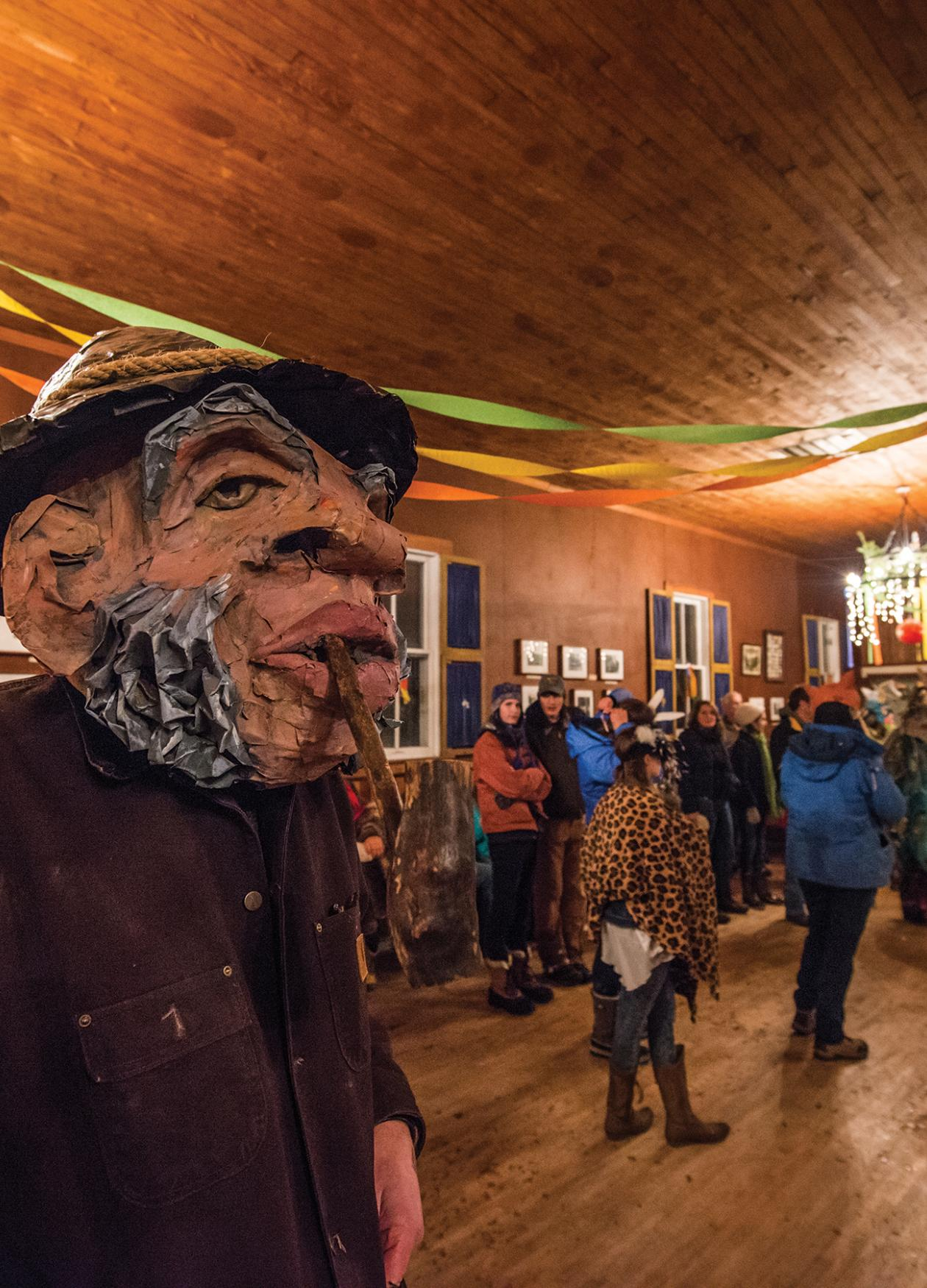 Color photo of a man wearing a mask at a costume festival, indoors.