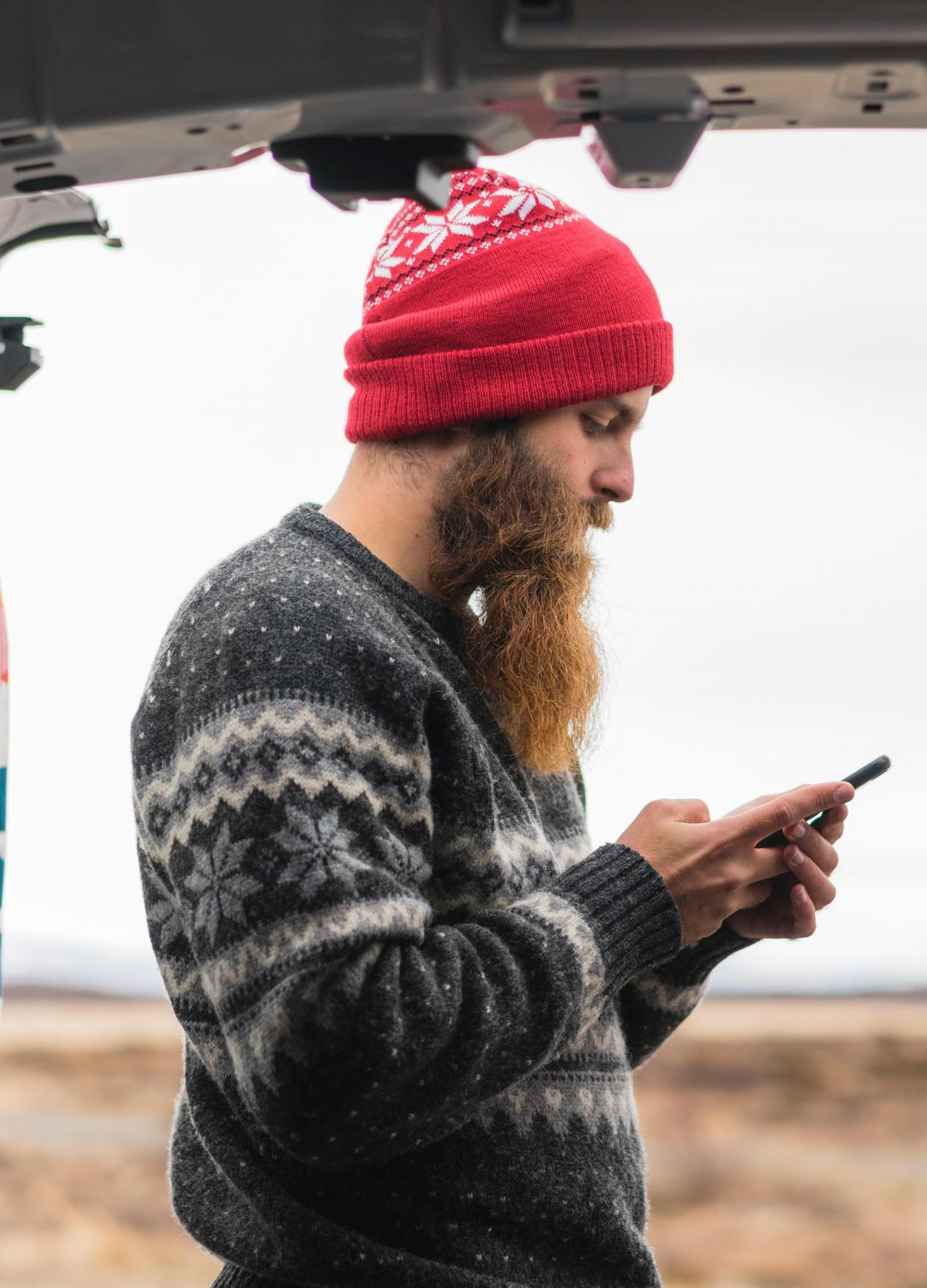 Hipster with his camper van and cell phone.