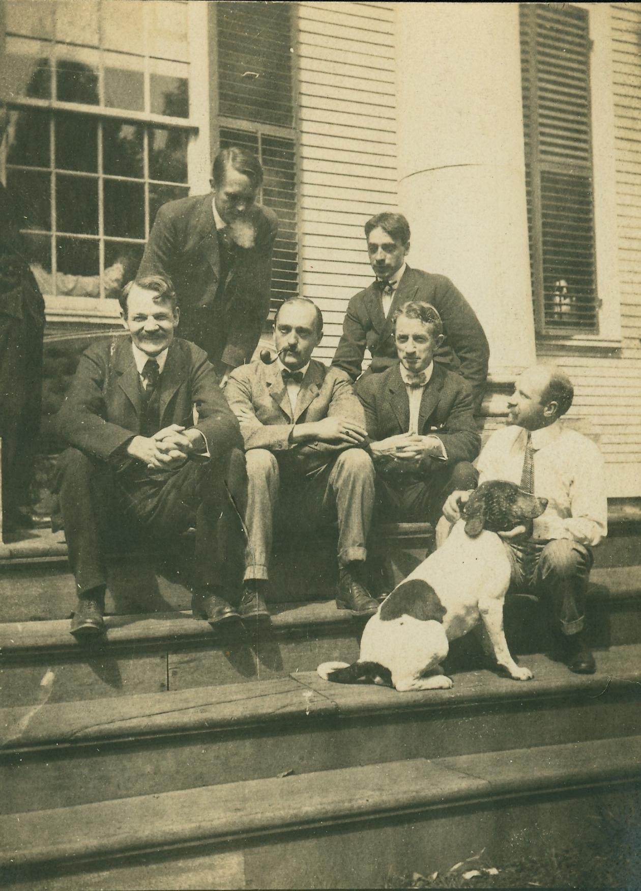Old photo of six men and a dog sitting on steps