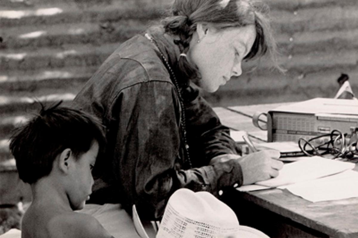 Woman writing on paper with a child next to her