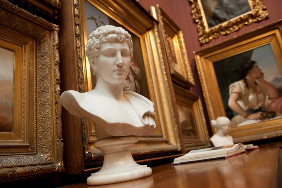 bust in front of picture frames