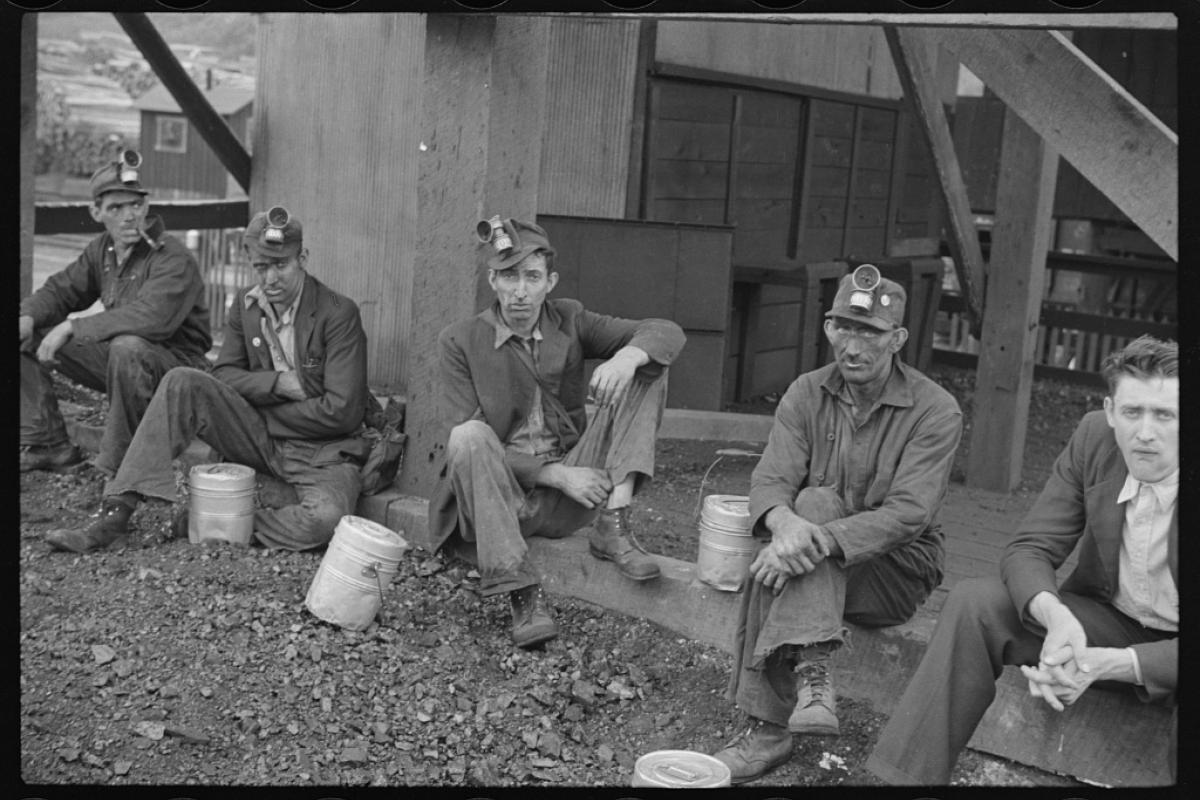 Black and white photo of five coal miners sitting on ground