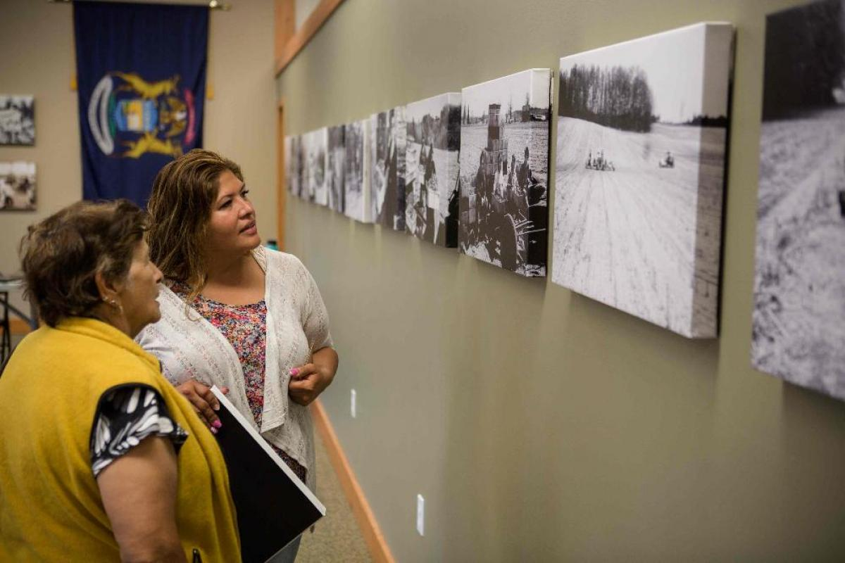 Two women looking at black and white photos on wall