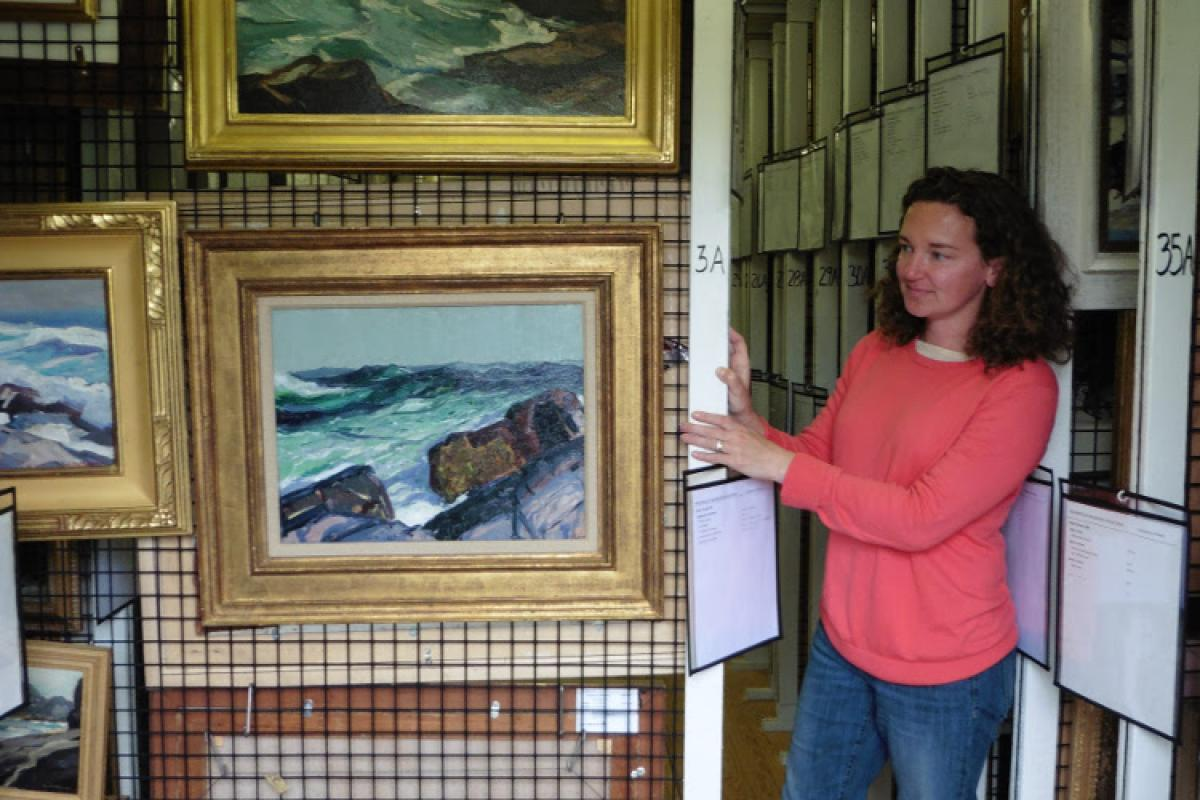 Woman standing next to framed paintings