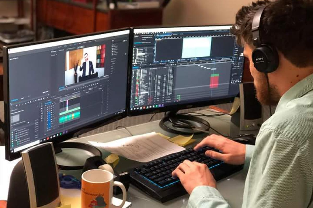 Man sitting at two computers, working on editing video