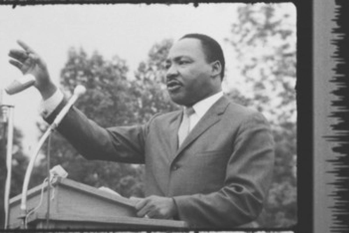 Black and white still of Martin Luther King, Jr. speaking
