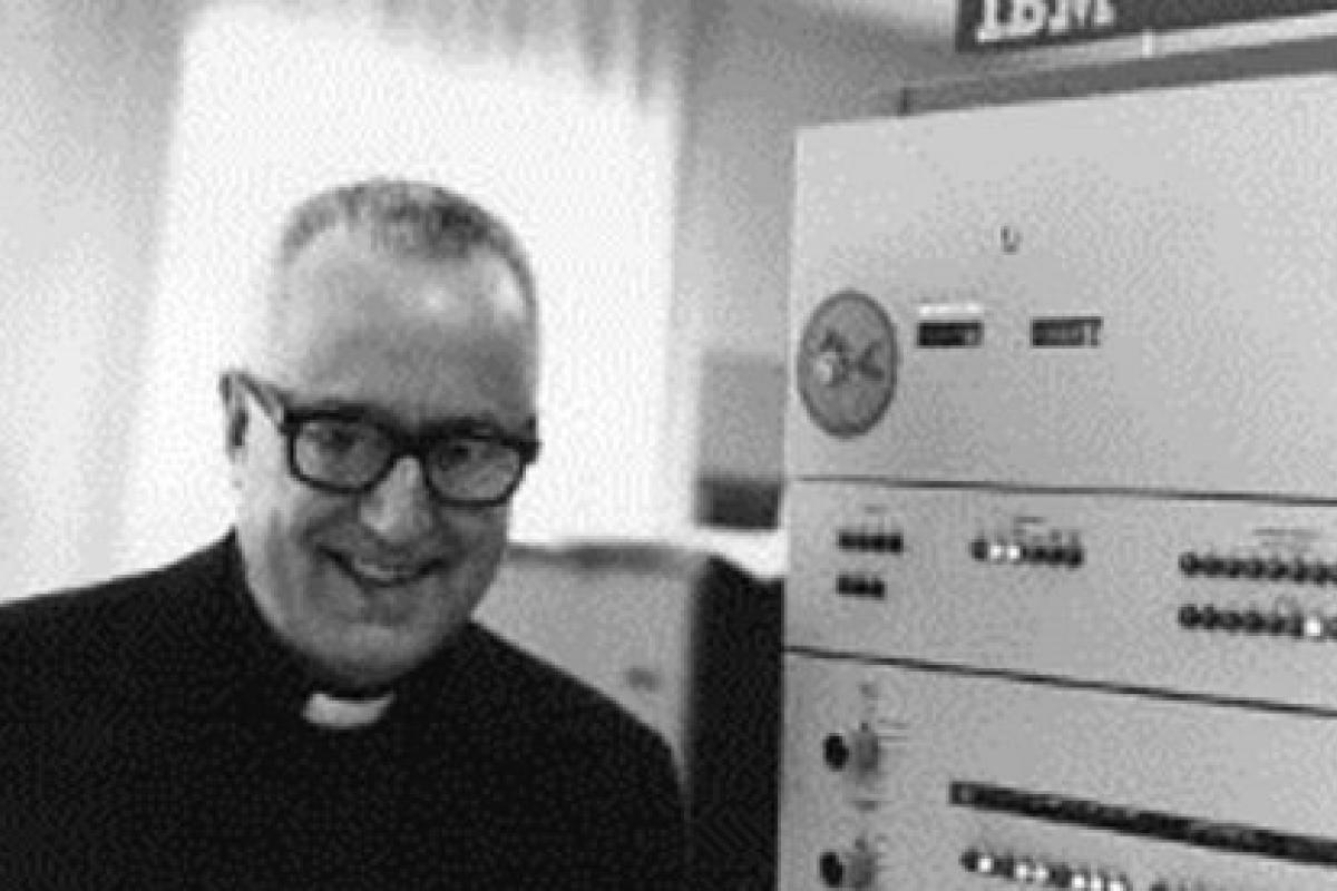 Photo of Father Roberto Busa next to a mainframe computer.
