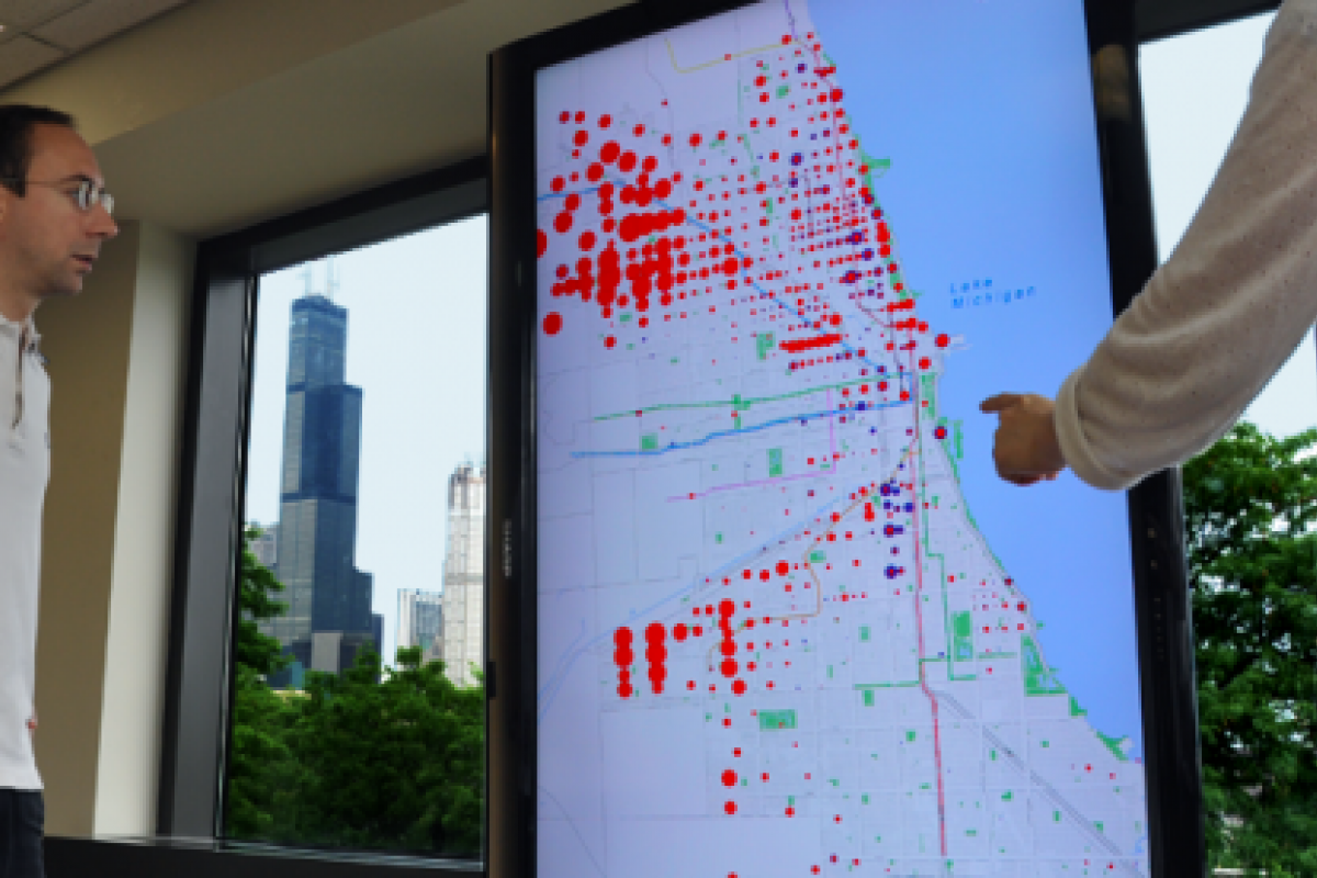 Large television display showing a map and scaled, colored dots which represent the relationships between different types of census data.