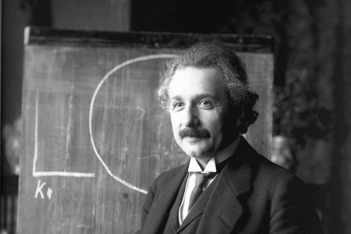 Black and white photo of Albert Einstein in front of chalkboard