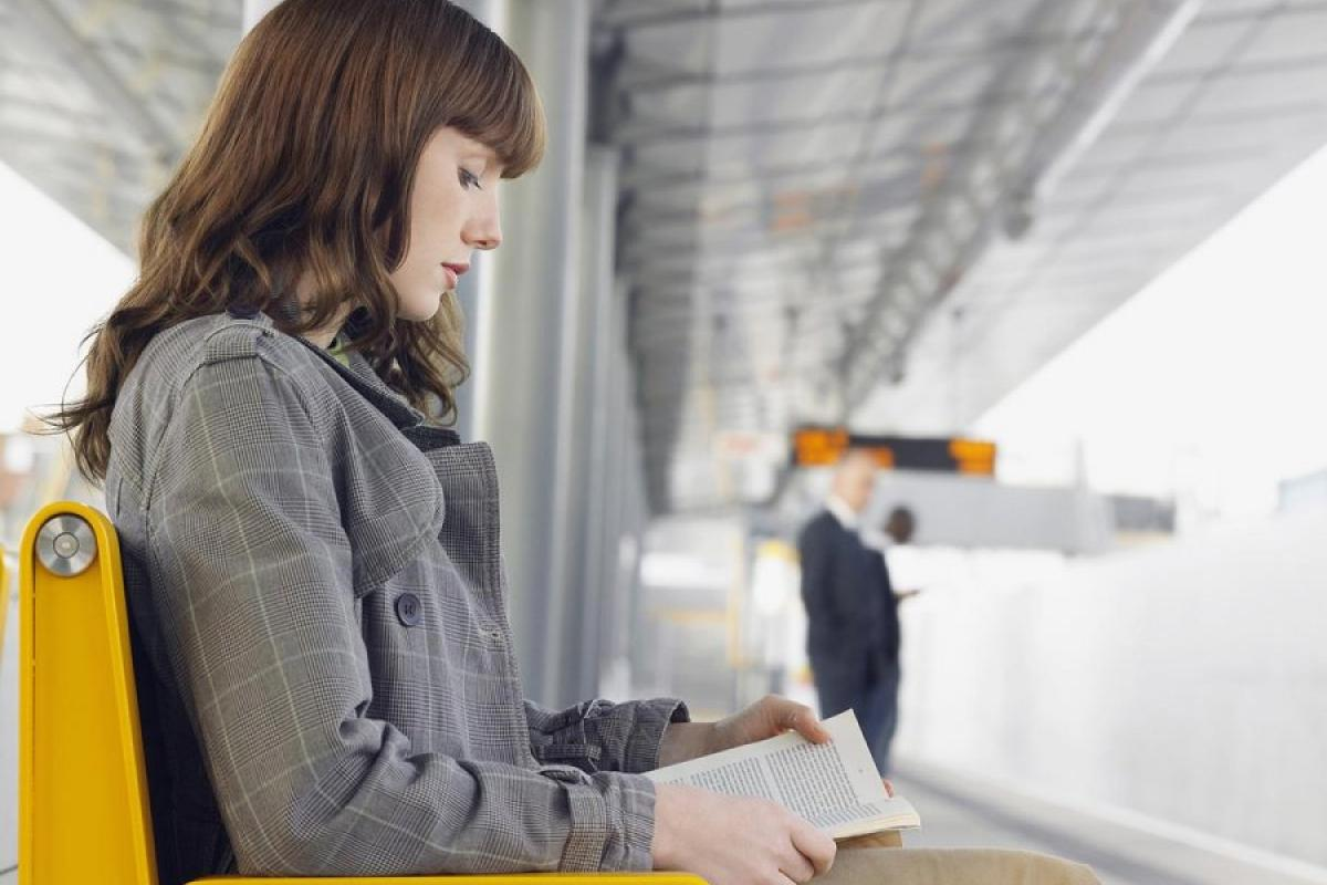 Dreamstime.com / Businesswoman Reading Book At Train Station Photo