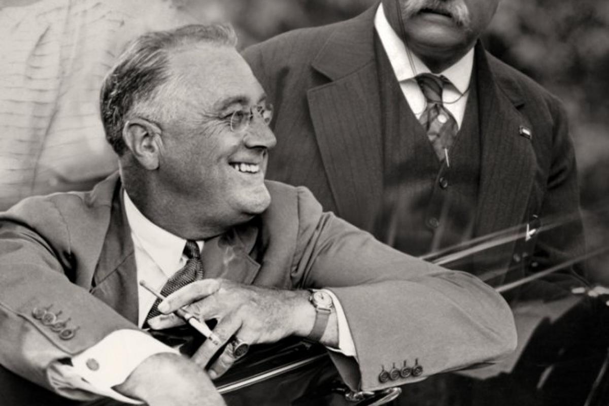 Franklin D. Roosevelt smiling from a car with cigarette holder in handf
