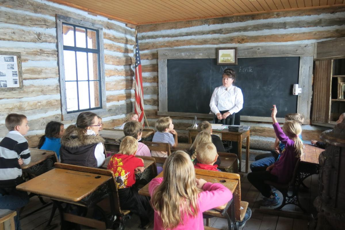 Children and teacher in a schoolhouse