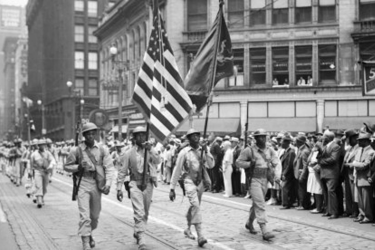 Four color guard from 372nd Infantry marching in front of soldiers	Four color guard from 372nd Infantry marching in front of soldiers