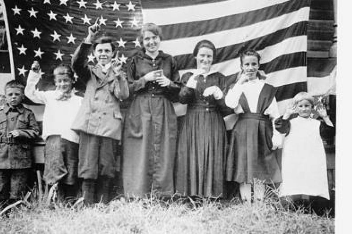 Black and white photograph of Students from the St. Rita's School for the Deaf, 1918, in front of the American flag