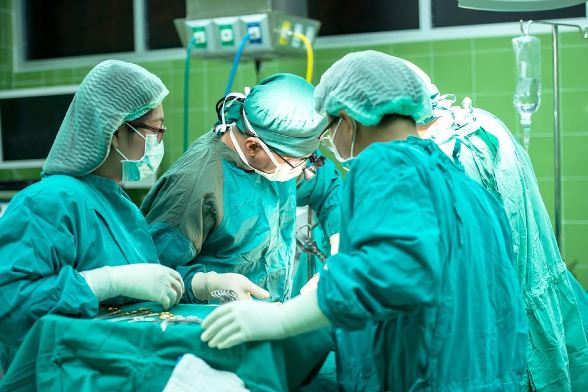 Several surgeons in green scrubs, participating in an operation