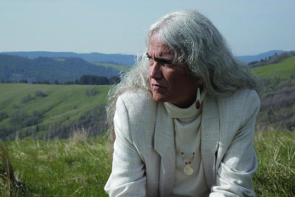 Native woman with gray hair looking into distance