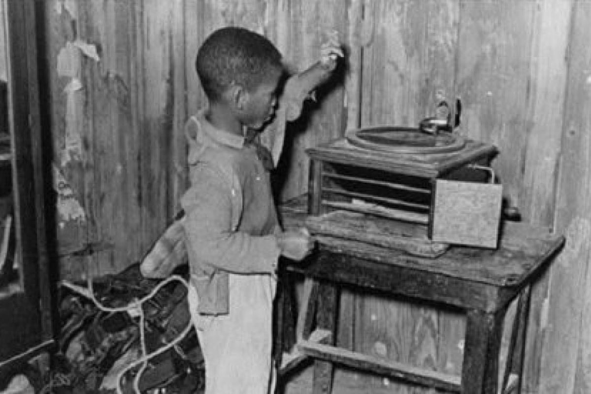 Black and white photo of a little black child playing with a phonograph in a cabin.