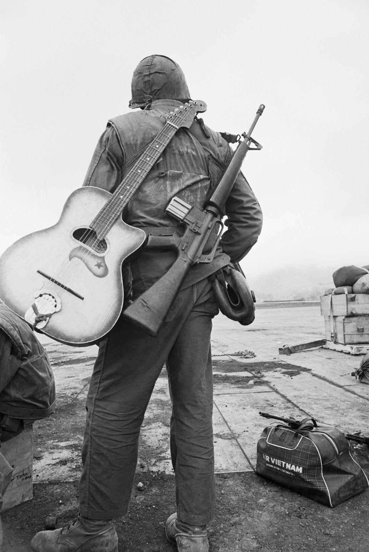 Black and white photo of a soldier with an M16 and a guitar slung over his back.