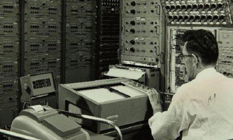 Black and white photo of a man sitting before a display and surrounded by large early computers.