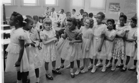 Black and white schoolgirls lined up in a classroom
